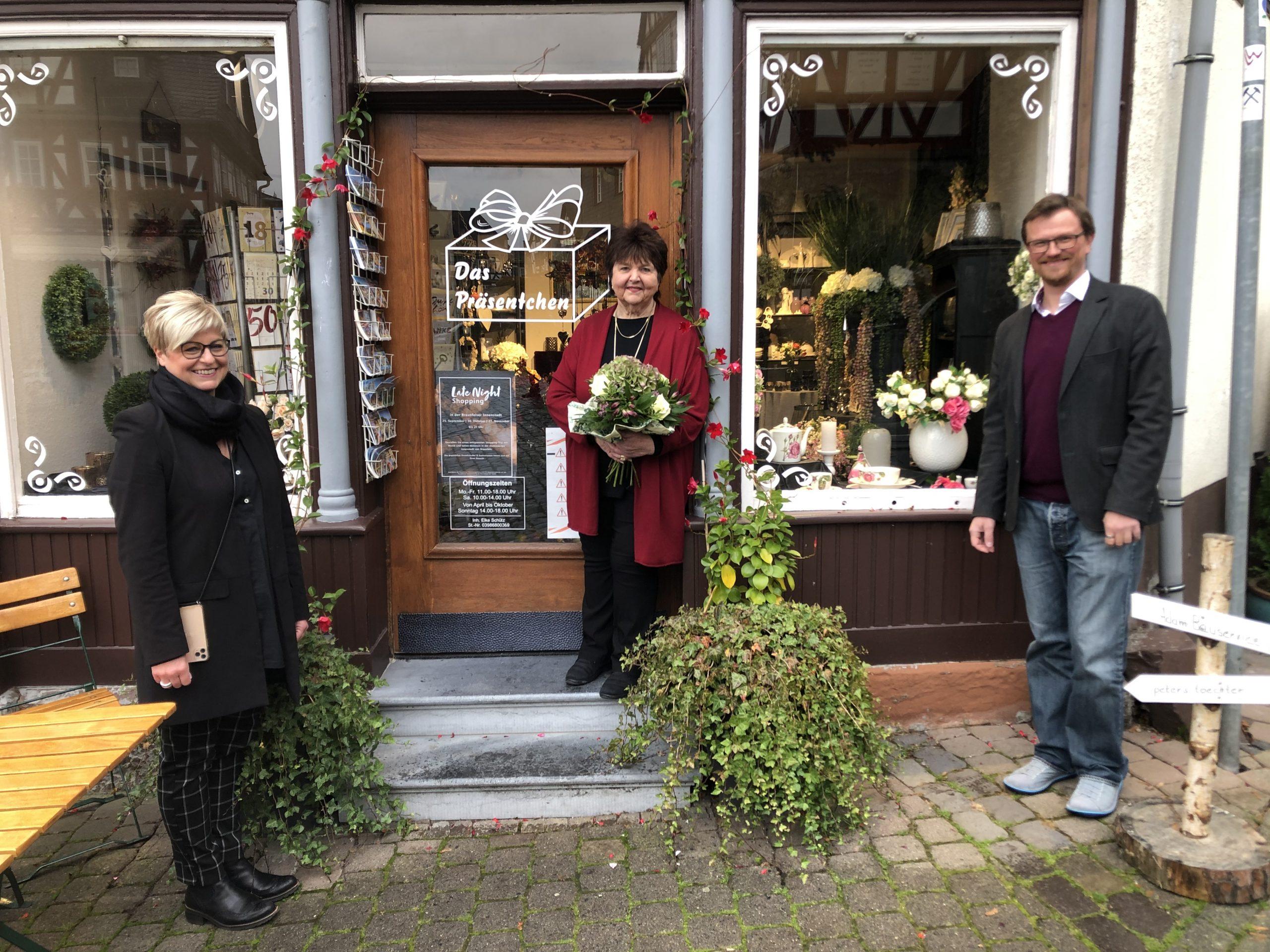 Regina Andermann (Interessengemeinschaft der Braunfelser Gewerbetreibenden e. V., links) und Philipp Borchardt (Braunfelser Kur GmbH, rechts) gratulieren Elke Schütz zum 25jährigen Jubiläum ihres Ladens.
